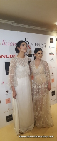 Sonam Kapoor poses in front of the sponsors' board at Divalicious London